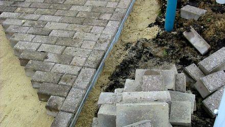 Opsluiting van bestrating door metalen of kunststof strips (opsluiten van klinkers, terrastegels, split- en grindpaden)