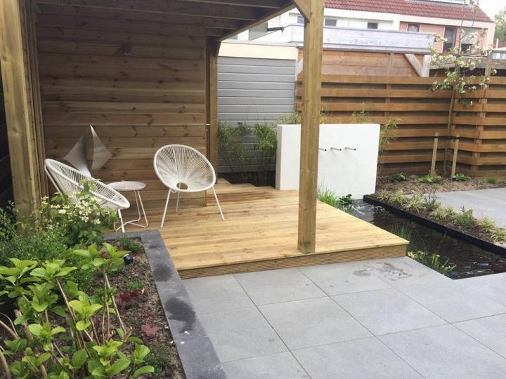 Moderne tuin met vijverwand met spuiters