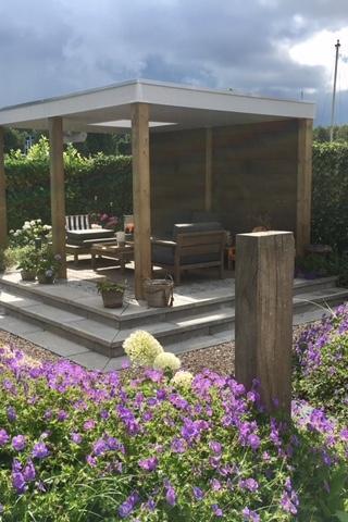 Loungetuin aan het water met verhoogd terras en overkapping