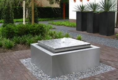 Moderne onderhoudsvrije voortuin met RVS watertafel